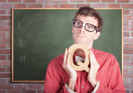 Bright male school teacher holding alphabet letter Q in school classroom with copyspace blackboard. Education question conceptual. photo