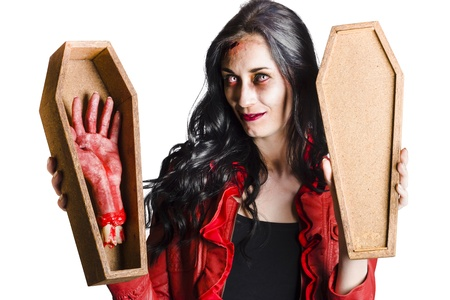 Beautiful vampire girl smiling and showing a bloody severed hand in a small coffin in a good mourning welcome concept photo