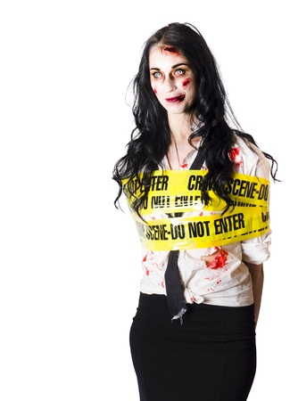 Zombie woman bleeding and injured at crime scene bound up with wide yellow tape isolated on white background photo