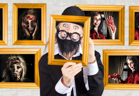Quirky photograph of a male art critic examining scary horror artworks inside a Halloween gallery display. Art of horror concept Stock Photo - 19145579