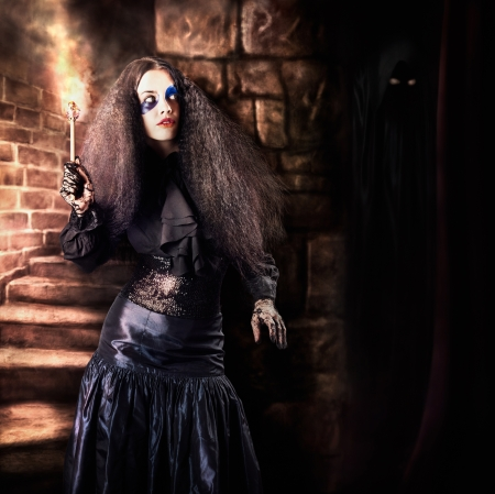 Medieval photo illustration of a jester woman holding torch lantern while walking inside a dark stone staircase deep inside the basement of a vintage haunted castle. Halloween concept illustration