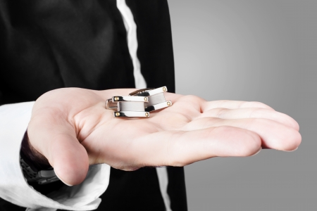 Photograph of a male model showcasing premium style cuff links in his hand photo