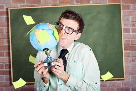 Nerdy business man holding earth world globe in school classroom when developing a plan for global expansion photo