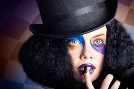 Face portrait of a female mad hatter wearing black top hat, bright colourful makeup with black manicured nails photo