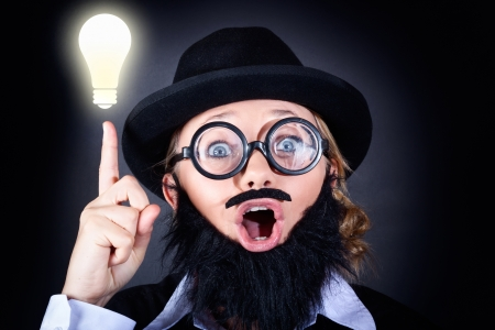 Crazy male scientist wearing nerd glasses, fake moe and plastic beard pointing up to bright lightbulb with expression of genius. Science Innovation concept photo