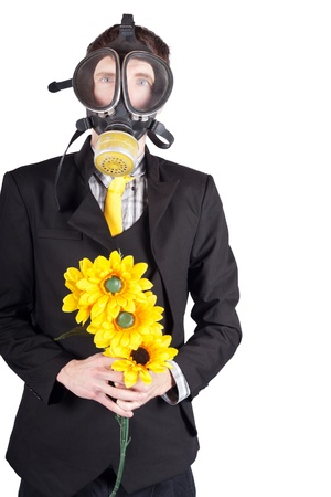 Environmental man in a gas mask holding a bouquet of yellow sun flowers.  photo