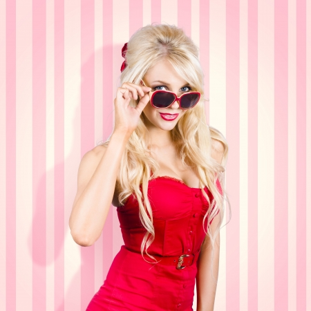 Beautiful young blond pin-up female wearing red dress with matching belt. Elegant fashion look photo