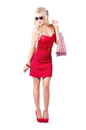 Fashionable blond woman in red dress with shopping bag over shoulder white background photo