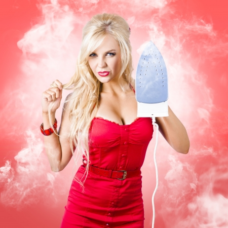 Emotional blond woman holding scorching hot iron in a depiction of hot housework. Red smoke background photo