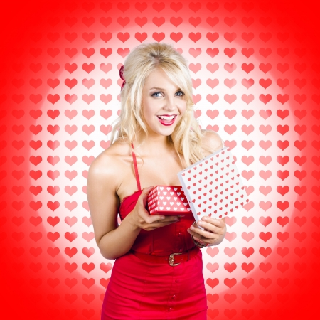 Valentines day - lady opening gift box with happy expression. Gift from the heart photo