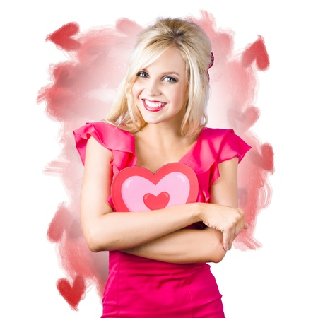 Smiling young woman hugging heart shaped cardboard photo