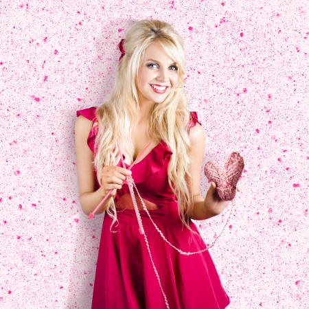 Sweet blond lady holding ball of heart shaped wool with knitting needles . Knitting love Stock Photo - 20097389