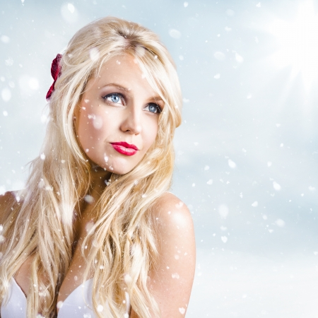 Enchanting picture of an amazing blonde winter woman watching the falling snow in elegant fashion style photo