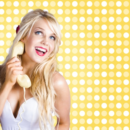 Lady listening to telephone gossip with classic fifties long blond hairstyle and make-up.  photo
