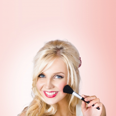 Delightful female model using blush powder makeup brush when demonstrating the art of Blushing. Pink Background photo