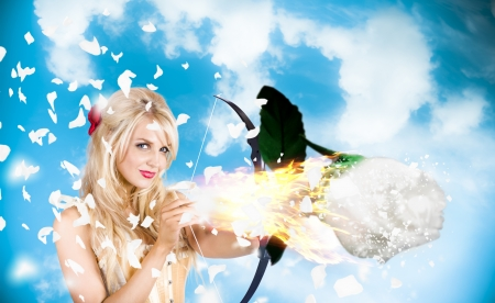 Stunning blond cupid girl shooting brilliant flame rose when aiming to light the spark of romance. Love is magical photo