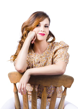 Attractive smiling young woman on antique wooden chair photo
