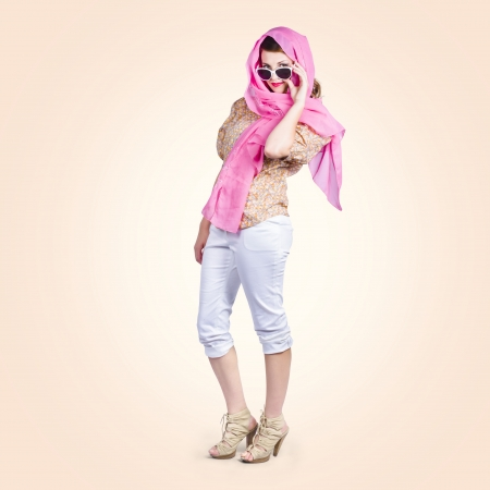 A 1960 pin-up culture girl wearing retro fashion head scarf, white cargo pants and sandals photo