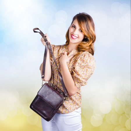 Cute young retro fashion model holding leather clutch bag with hand to chest. photo