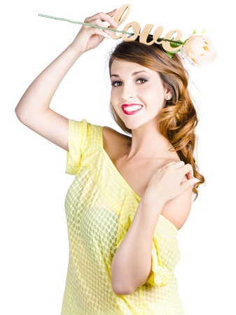 Beautiful woman in yellow dress holding message of love above her head and a single white rose. photo