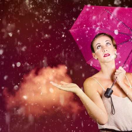 Stylish woman with open palm feeling the downpour of falling rain during the humidity of summer. Retro fashion storm photo
