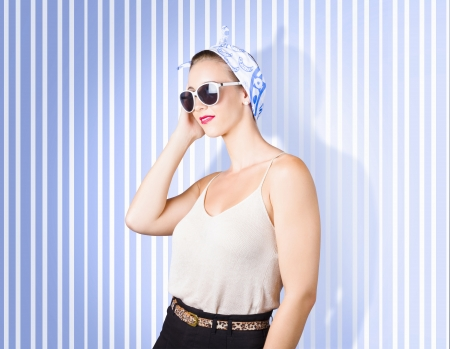 Fashion glamour girl in perfect make-up accessorising on retro striped background photo