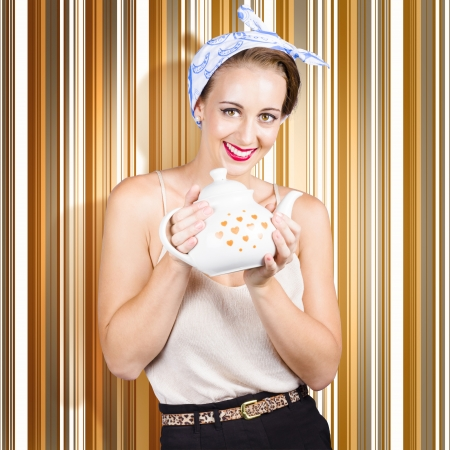 Portrait of a friendly cafe waitress holding tea teapot when serving drinks with a smile. Retro striped background photo