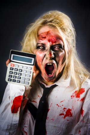 Shocked finance accountant holding calculator when working out a monstrous tax debt.  photo