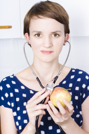 Attractive young woman doctor in blue dress holding stethoscope against an apple photo