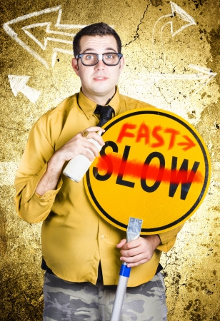 Male office worker holding slow sign painted over with fast when showing direction to fast track productivity photo