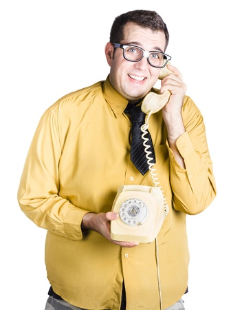 worried looking man on an old fashioned corded phone, taking important call photo