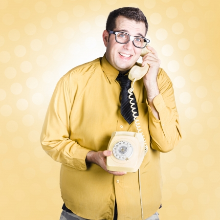 Frightened male staff member talking with look of uncertainty on retro turn-dial telephone. Important phone call concept photo