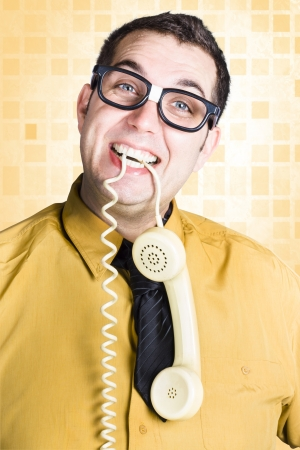 Friendly business person biting telephone cord between his teeth Stock Photo - 20035623