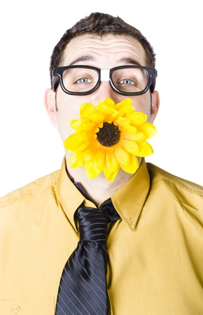 Nerdy young man with yellow sun flower in mouth on white background photo