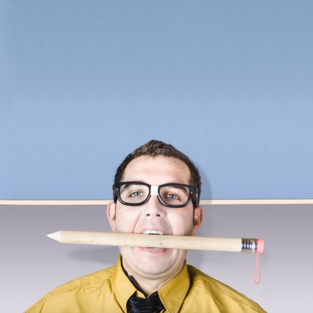 Geeky businessman holding massive pencil in mouth photo