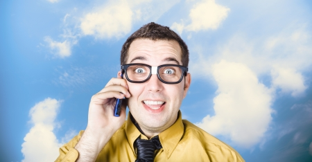 Excited nerd businessman talking the talk on mobile smartphone on cloud background photo