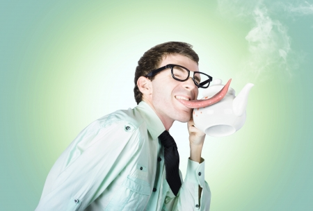 Man licking a steaming hot kettle with his long tongue photo