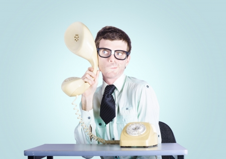 Business man holding enlarged telephone receiver photo