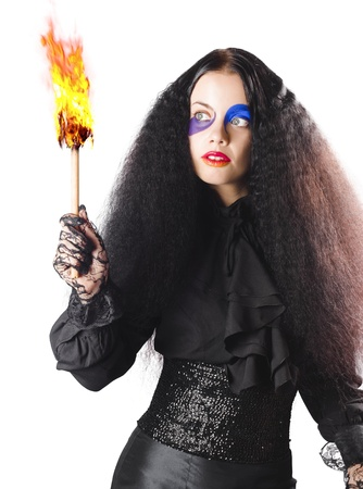 Woman in black medieval costume with face paint and burning fire torch on white background photo