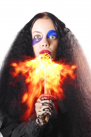 Scary woman with long black hair breathing or blowing fire from mouth on white background photo