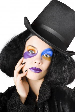 Young woman with top hat, face makeup and long black hair in jester costume photo
