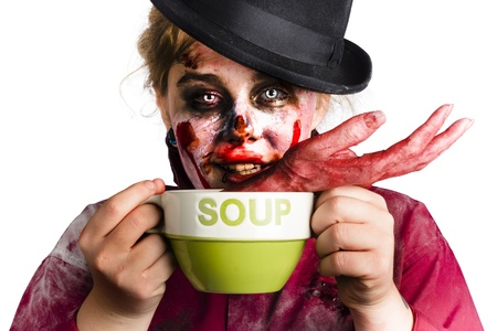 A woman in zombie costume and make up eating a soup with a human hand photo