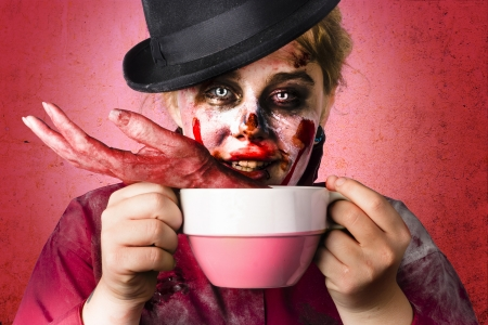 Creepy female zombie holding big soup cup containing severed and mutilated hand. Halloween cooking concept photo