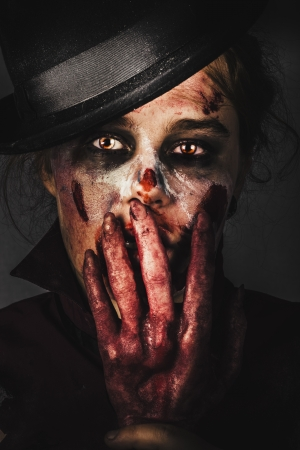 Dark frightening face of fear. Zombie holding severed hand to shocked face when killing the night with fright photo