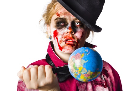 Beaten and bloody zombie woman holding a globe stabbed with a knife. photo