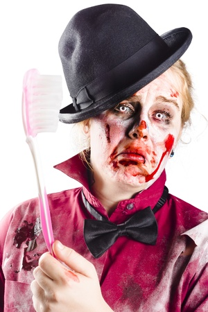 Bloody, beaten and diseased woman holding a toothbrush. Dental disease photo