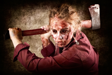 Frightful portrait of a grunge zombie holding rusty old axe when chopping up Halloween victims of horror photo