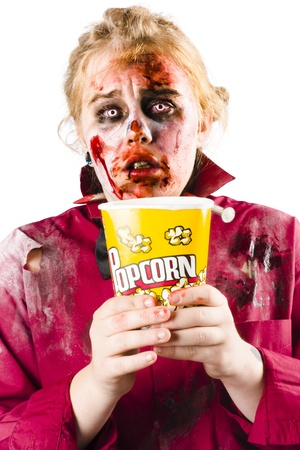 A woman in zombie makeup and outfit watching a scary movie with a bucket of popcorn. photo