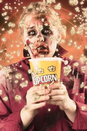 Frightened female ghoul splashing popcorn everywhere in the cinema. Scary film concept photo