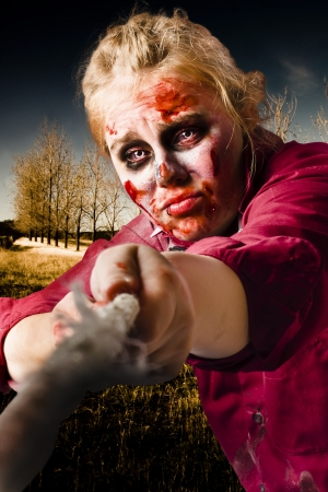 Female zombie pulling on a tug of war rope with cuts and bruises in a show of courage, strength and resilience. Determined spirit photo